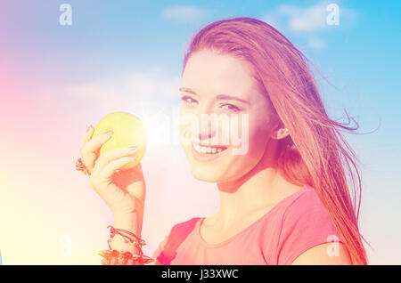 Portrait happy woman with green apple smiling enjoying good weather sunny summer day by the sea - Stock Photo