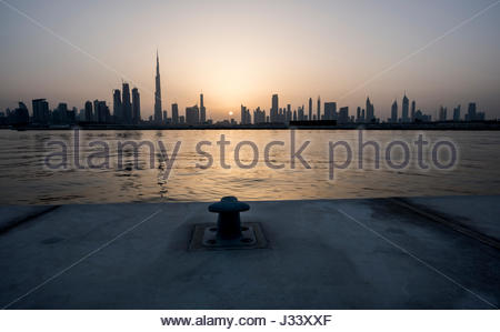 Silhouette of Dubai during a nice sunset on the city, view from the water canal with anchor hook in foreground, - Stock Photo