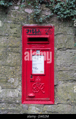 a view of black graffiti on a pill post letter box in a stone wall - Stock Photo