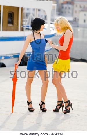 Talk blonde and black-haired attractive teenagers smile happy smiling sunny after rain umbrella in hand highheels - Stock Photo