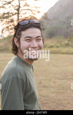 asian younger man toothy smiling face happiness emotion standing outdoor - Stock Photo