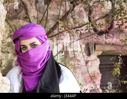 Portrait of beautiful and enigmatic young woman wearing hiyab looking at camera. - Stock Photo