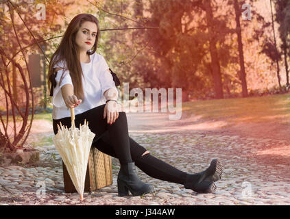 Full length portrait of young woman sitting on vintage suit case  with an umbrella. - Stock Photo
