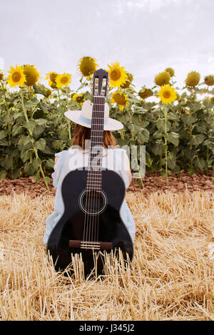 Young woman with her guitar in a field of sunflowers - Stock Photo