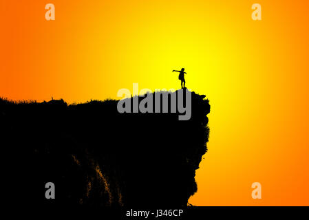 Black silhouette on orange and yellow background of woman tourist standing arms outstretched happy with success - Stock Photo