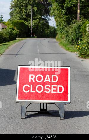 Road sign on a street showing a road closure - Stock Photo