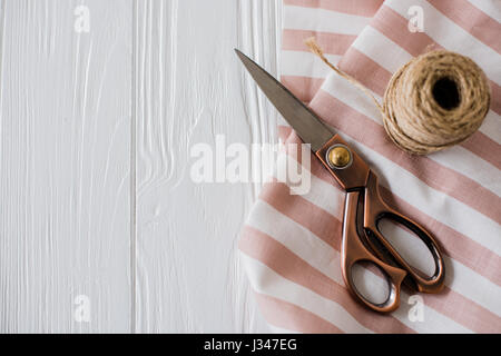 Beautiful scissors, striped fabric and twine spool on a white tabletop board with copyspace - Stock Photo