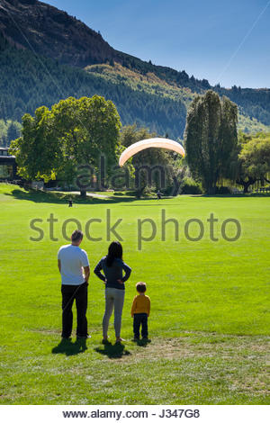 Man, woman and child watching a paraglider landing on the field at Queenstown Recreation Ground, Queenstown, Otago, - Stock Photo