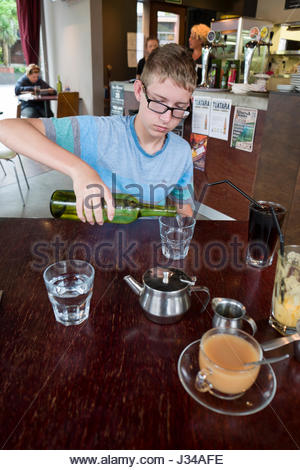 Young teenage boy pouring himself a glass of water from a green bottle, Queenstown, Otago, South Island, New Zealand - Stock Photo