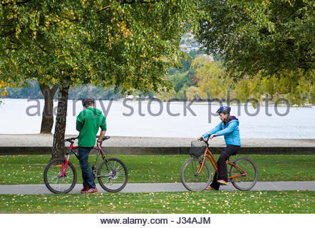 Man and woman on bicycles with Lake Wakatipu in the background, Queenstown, Otago, South Island, New Zealand - Stock Photo