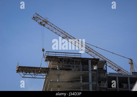 Tower crane moves a flying form used to support concrete pours in tall buildings. - Stock Photo