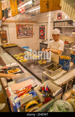KYOTO, JAPAN - OCTOBER 8, 2016: Unidentified man preparing okonomiyaki in Kyoto, Japan. Okonomiyaki is a Japanese - Stock Photo