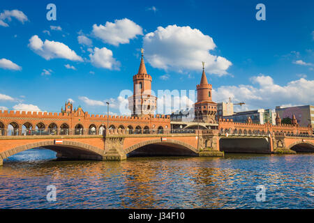 Beautiful view of famous Oberbaum Bridge crossing the Spree river on a sunny day with blue sky and clouds in summer, - Stock Photo
