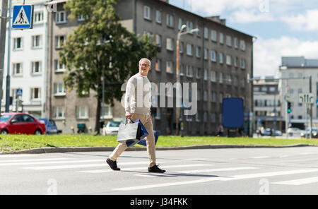 senior man with shopping bags walking on crosswalk - Stock Photo