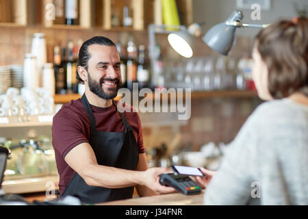 barman and woman with card reader and smartphone - Stock Photo