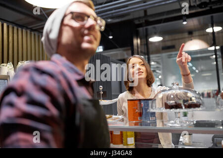 happy woman showing something to bartender at cafe - Stock Photo