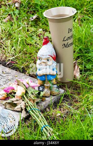 Garden gnome on a grave as a memorial.. - Stock Photo