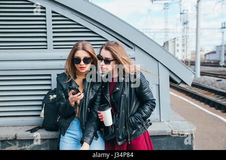 Two Women Talking in the City.Outdoor lifestyle portrait of two best friends hipster girls wearing stylish Leather - Stock Photo