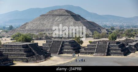 Teotihuacan, Mexico - 21 April 2017: Tourists atop and climbing the Pyramid of the Sun with other tourist in plaza - Stock Photo