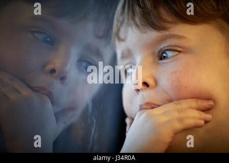 Little boy looking out the window on a train in Boston, America - Stock Photo