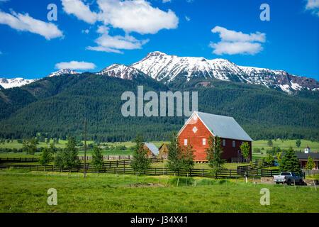 Red barn near Wallowa Mountains in Oregon - Stock Photo