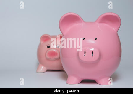 A large pink piggy bank in front of a smaller one - Stock Photo