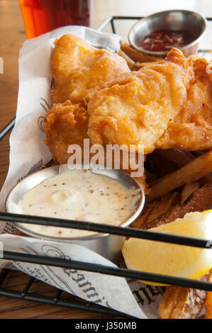 Close-up of a basket of fish and chips, or french fries, served with tartar sauce, catsup, and a cold beer - Stock Photo