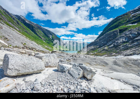 At the mouth of the Niggardsbreen glacier, in a glacial valley surrounded by mountains and waterfalls. Boulders - Stock Photo
