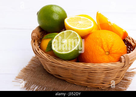 Basket of Citrus Fruits on white wooden background - Stock Photo