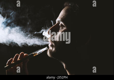 Young man holding and vaping an electronic cigarette, e-cig, ecigarette. - Stock Photo