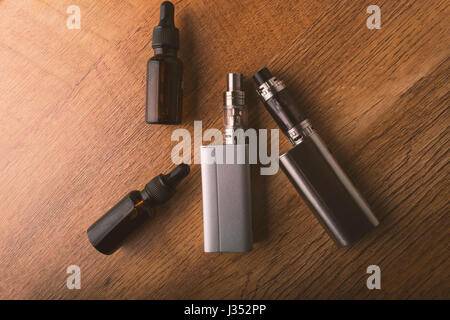 e cigarette with e liquid bottles for vaping devices, electronic cigarette or e cig on a wooden background. - Stock Photo
