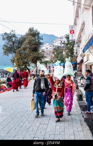 Indian lifestyle: local women carrying large heavy loads in sacks on their heads in the street in McLeodGanj, Dharamshala, - Stock Photo