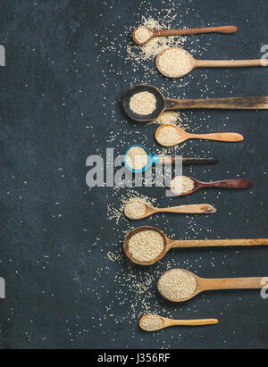 Quinoa seeds in spoons over black stone background, copy space - Stock Photo