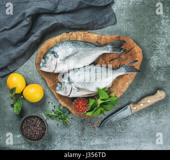 Uncooked sea bream fish with lemon, herbs, spices, grey background - Stock Photo