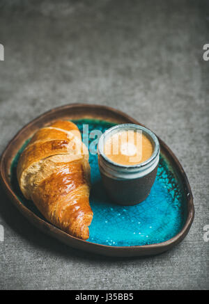Cup of espresso and croissant in blue tray, grey background - Stock Photo