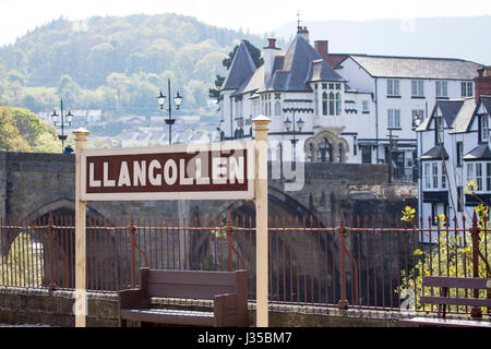 Llangollen train station sign with the town in the background and bridge that crosses the River Dee in Llangollen, - Stock Photo