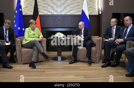 Russian President Vladimir Putin sits with German Chancellor Angela Merkel before the start of bilateral discussions - Stock Photo