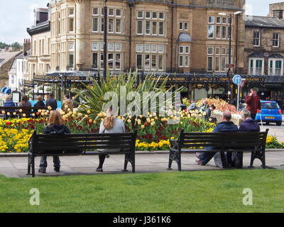 People relaxing in the sun in gardens in the centre of the Montpellier District of Harrogate, Yorkshire, UK, with - Stock Photo