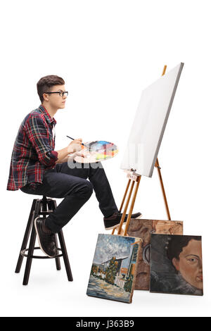 Profile shot of a teenage painter with a paintbrush and a palette looking at a blank canvas isolated on white background - Stock Photo