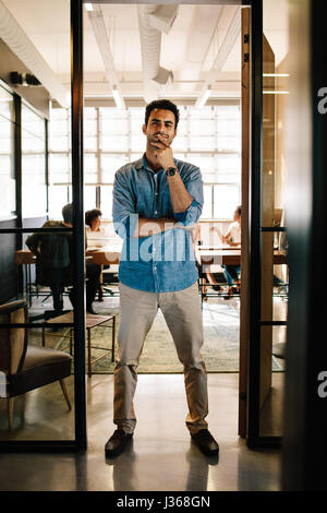 Full length portrait of creative young man standing in doorway of office. Caucasian male executive in office with - Stock Photo