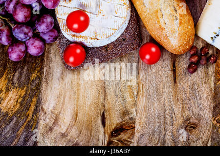 assorted food ingredients - cheese, bread, tomatoes and grapes and vertical copyspace ready to be filled with some - Stock Photo