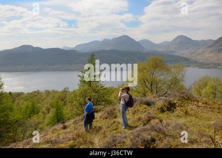 A couple gaze over Loch Lomond from a hilltop near Inversnaid, Scotland, UK - Stock Photo