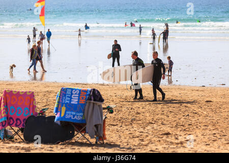 Newquay, UK. beach goers enjoy the sun on a bright and sunny spring afternoon on Fistral Beach in Newquay. Surfers - Stock Photo