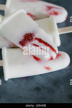 Homemade ice cream popsicles with fresh strawberries on the grey background - Stock Photo