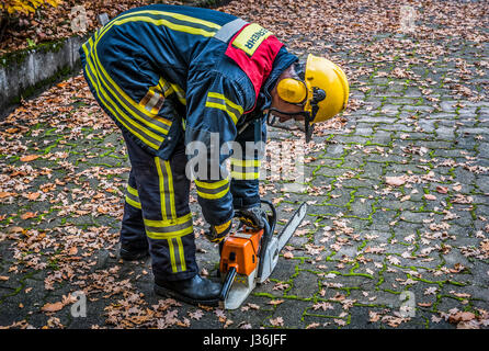 Firefighter in action with a chain saw - HDR - Stock Photo