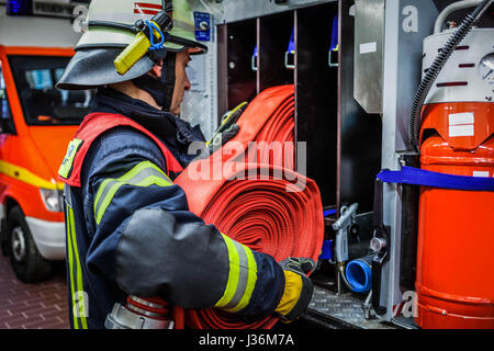 Firefighter in the fire station with a water hose in the hand - HDR - Stock Photo