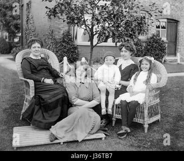 Portrait of the females from an Edwardian family, three adults and two children, sitting in a garden in 1910. On - Stock Photo