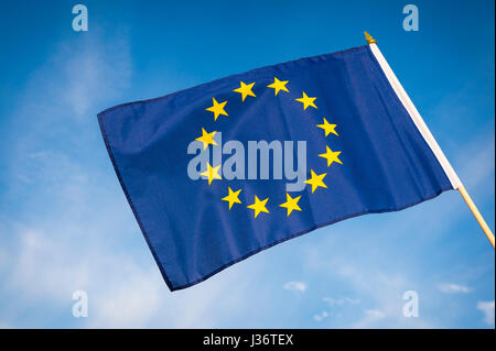 EU European Union flag flying outdoors in bright blue sky - Stock Photo