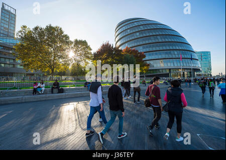 LONDON - OCTOBER 31, 2016: Visitors walk past the rounded form of the City Hall building on the South Bank of the - Stock Photo