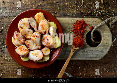 high-angle shot of an earthenware plate with pulpo a la gallega, a recipe of octopus typical in Spain served on - Stock Photo